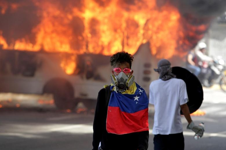 Demonstrators stand next to a bus burns near a protest against Venezuela's President Nicolas Maduro's government in Caracas, Venezuela, May 13, 2017.  REUTERS/Christian Veron