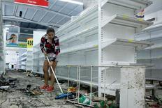 Una mujer limpia un comercio que fue saqueado en la ciudad de San Cristóbal. 17 de mayo de 2017. Varios lugares en Venezuela comenzaban a sufrir escasez de gasolina el miércoles, porque refinerías del país petrolero enfrentan nuevos problemas de operación y algunos envíos han sido bloqueados por las protestas de la oposición. REUTERS/Carlos Eduardo Ramirez