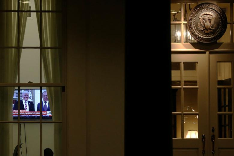 A television plays a news report on President Trump's recent Oval Office meeting with Russia's Foreign Minister Sergei Lavrov as night falls on offices and the entrance of the West Wing White House. REUTERS/Jonathan Ernst