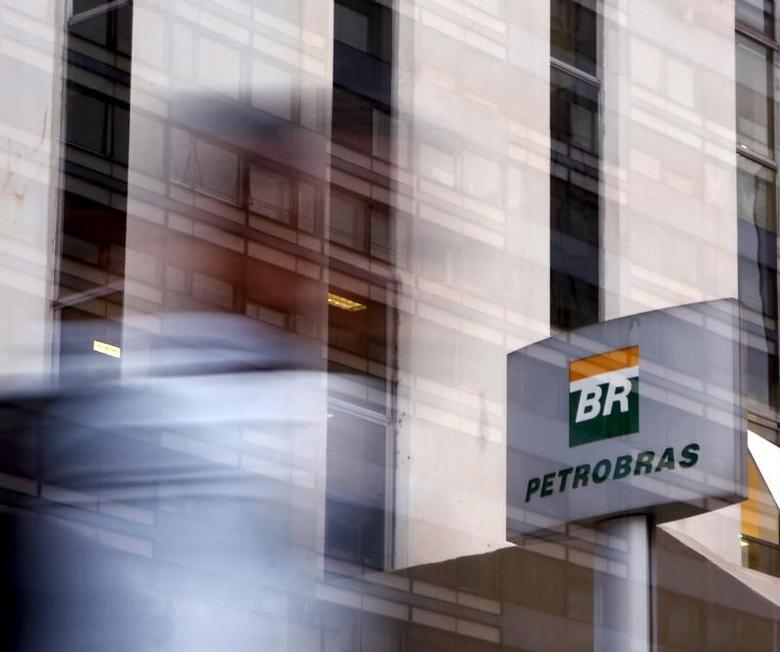 A person walks past the Petrobras logo in front of the company's headquarters in Sao Paulo April 23, 2015. REUTERS/Paulo Whitaker