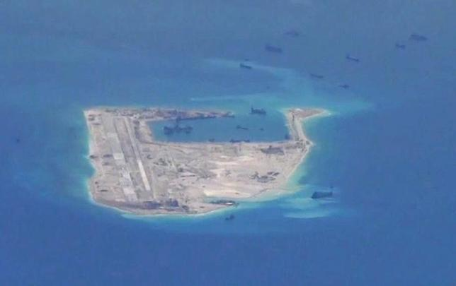 Chinese dredging vessels are purportedly seen in the waters around Fiery Cross Reef in the disputed Spratly Islands in the South China Sea in this still image from video taken by a P-8A Poseidon surveillance aircraft provided by the United States Navy May 21, 2015. U.S. Navy/Handout via Reuters/Files