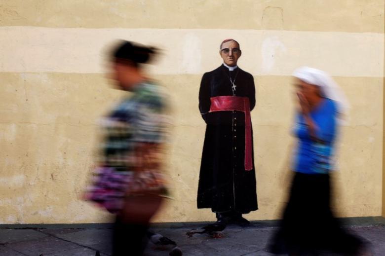 People walk by a graffiti of the murder of late Archbishop of San Salvador Oscar Arnulfo Romero in San Salvador, El Salvador, May 18, 2017. REUTERS/Jose Cabezas