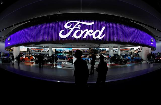 FILE PHOTO: People walk by the Ford display during the North American International Auto Show in Detroit, Michigan, U.S., January 10, 2017. REUTERS/Mark Blinch