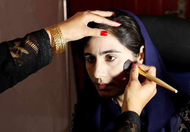 Shamla Neazi, 20, Afghan presenter, receives make-up before her broadcast at the Zan TV station (women's TV) in Kabul, Afghanistan May 8, 2017. REUTERS/Mohammad Ismail
