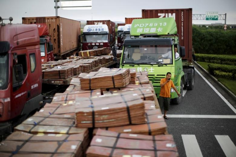 FILE PHOTO: Trucks carrying copper and other goods are seen waiting to enter an area of the Shanghai Free Trade Zone, in Shanghai in this September 24, 2014 file photo. REUTERS/Carlos Barria/File Photo