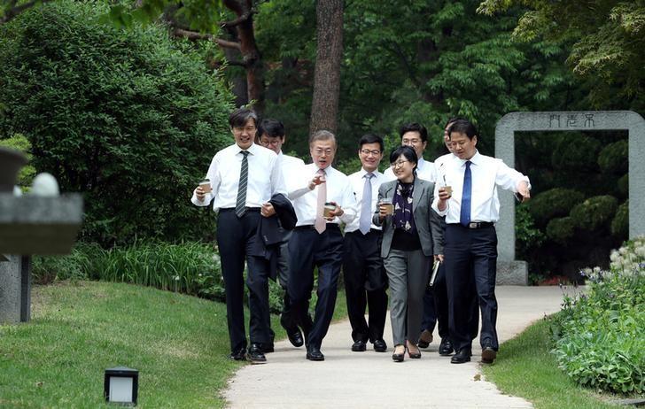 South Korean President Moon Jae-in takes a walk with senior presidential secretaries at the Presidential Blue House in Seoul, South Korea, May 11, 2017. Picture taken on May 11, 2017.   Yonhap via REUTERS