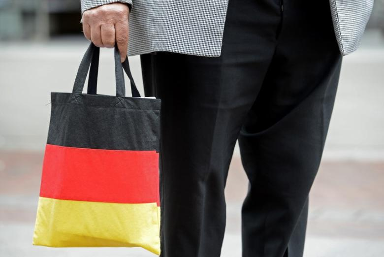 FILE PHOTO: A man carries a shopping bag in the colours of the German national flag in downtown Hanover June 26, 2012. REUTERS/Fabian Bimmer