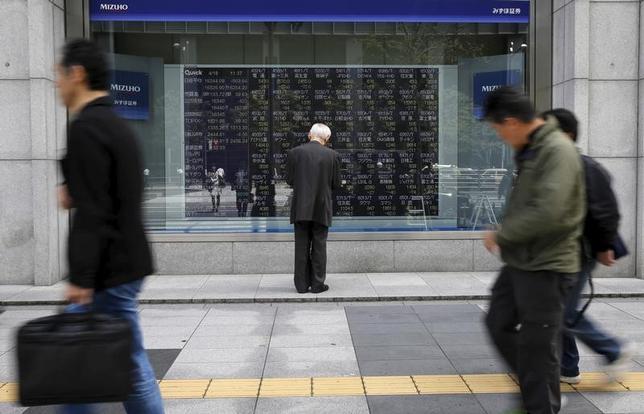 5月22日、今週の東京株式市場は、一進一退の展開が見込まれる。写真は株価ボードを眺める男性、都内で2016年4月撮影(2017年 ロイター/Toru Hanai)