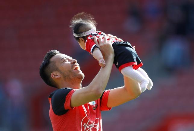 5月21日、サッカーのイングランド・プレミアリーグ、吉田麻也所属のサウサンプトンはホームでストークに0─1で敗れた。吉田はフル出場した。写真は試合後に子どもを抱きかかえる吉田(2017年 ロイター/Peter Nicholls)