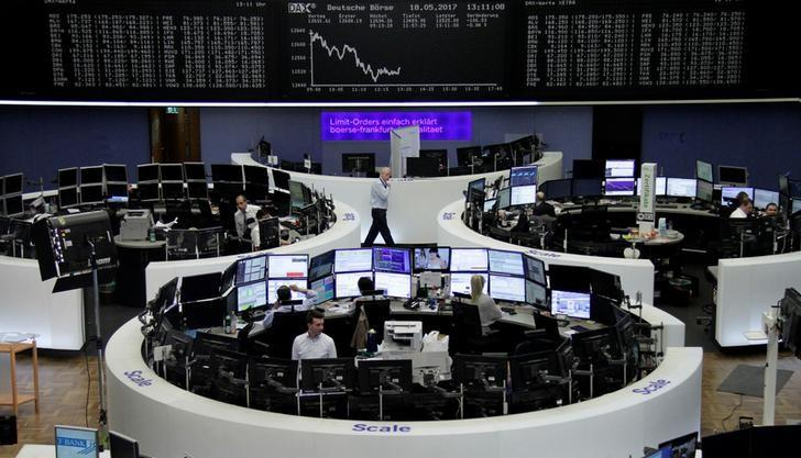 FILE PHOTO: Traders work in front of the German share price index, DAX board, at the stock exchange in Frankfurt, Germany, May 18, 2017. REUTERS/Staff/Remote