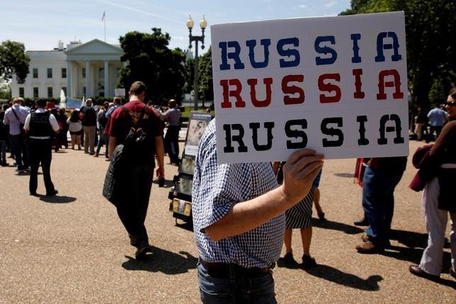 5月22日、トランプ米大統領に解任されたコミー前FBI長官は、24日に予定されていた下院監視・政府改革委員会の公聴会での証言を延期した。前長官の解任に反対する人々、ホワイトハウス前で10日撮影(2017年 ロイター/Jonathan Ernst)