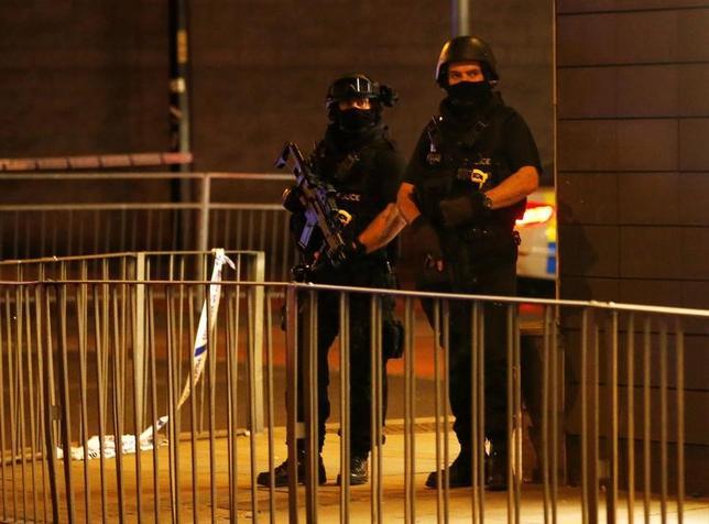 5月23日、英国のメイ首相はマンチェスターのコンサート会場で起きた爆発事件を受け、23日午前9時(日本時間午後5時)に安全保障会議を開く。写真は同コンサート会場の外の規制線付近に立つ武装警官。(2017年 ロイター/Andrew Yates)