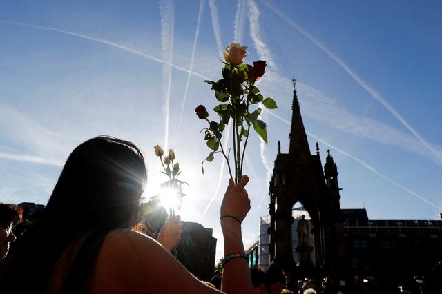 A woman holds flowers as she takes part in a vigil for the victims of an attack on concert goers at Manchester Arena, in central Manchester, Britain May 23, 2017. REUTERS/Darren Staples