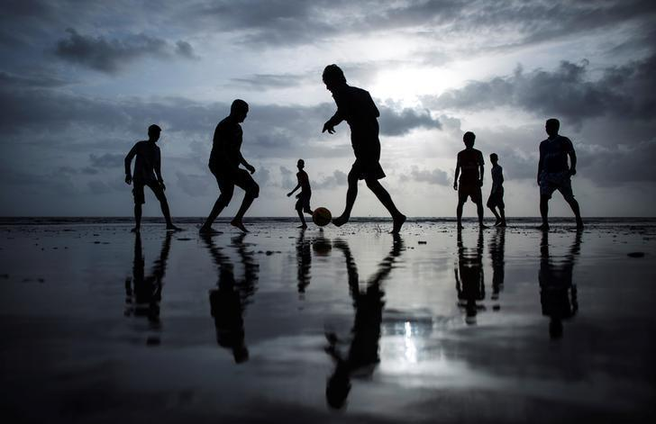 People are silhouetted as they play football at a beach along the Arabian Sea in Mumbai, June 25, 2014. REUTERS/Danish Siddiqui/Files
