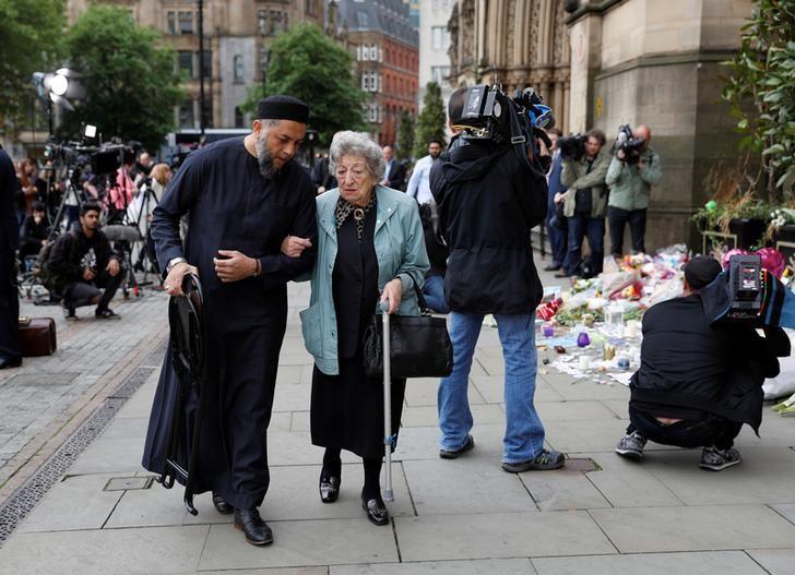 A Muslim man named Sadiq Patel and a Jewish woman named Renee Rachel Black walk by floral tributes in Albert Square in Manchester, Britain May 24, 2017. REUTERS/Darren Staples