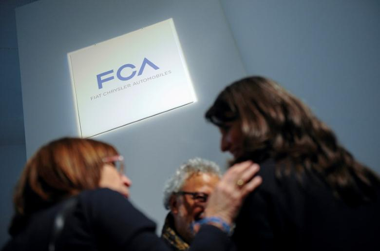 FILE PHOTO: People talk as they stand next to a logo of Fiat Chrysler Automobiles (FCA) in Turin, Italy on March 31, 2014.  REUTERS/Giorgio Perottino/File Photo