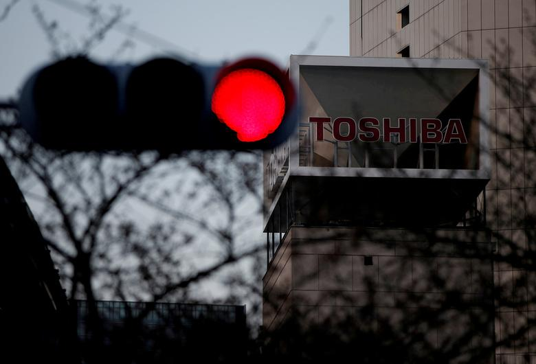 FILE PHOTO: The logo of Toshiba Corp is seen behind a traffic light at the company's headquarters in Tokyo, Japan March 29, 2017. REUTERS/Issei Kato/File Photo