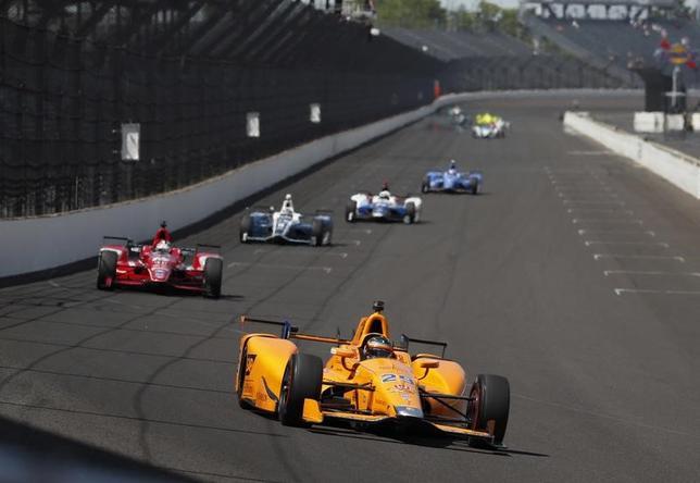 5月24日、自動車レースF1、個人総合優勝2回の実績を有し、28日決勝のインディ500にスポット参戦するフェルナンド・アロンソ(手前)は、両レースをクロスオーバーさせることは米国とF1のレース界双方に寄与すると述べた。米インディアナポリスで22日撮影(2017年 ロイター/Brian Spurlock-USA TODAYSports)