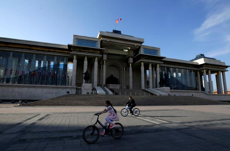 People cycle past the parliament building at Genghis Square in Ulaanbaatar, Mongolia, June 27, 2016. REUTERS/Jason Lee