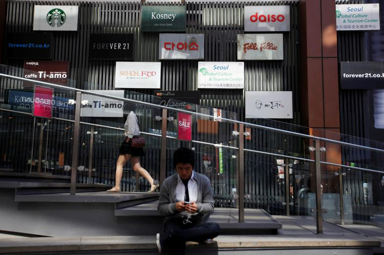 FILE PHOTO: A man uses his mobile phone in front of advertisement boards in central Seoul October 11, 2012. REUTERS/Kim Hong-Ji/File Photo