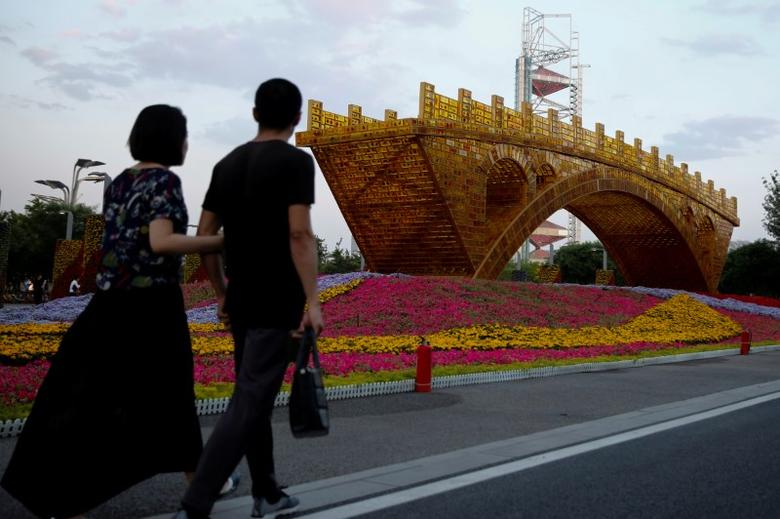 People walk past the installation ''Golden Bridge on Silk Road'' by artist Shuyong set up ahead of the Belt and Road Forum in Beijing, China May 10, 2017. REUTERS/Thomas Peter