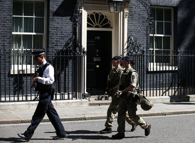 Armed soldiers and a police officer walk past 10 Downing Street in London, Britain, May 25, 2017. REUTERS/Neil Hall