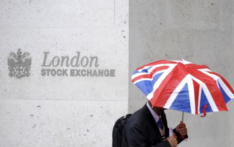 FILE PHOTO - A worker shelters from the rain under a Union Flag umbrella as he passes the London Stock Exchange in London, Britain, October 1, 2008.  REUTERS/Toby Melville/File Photo