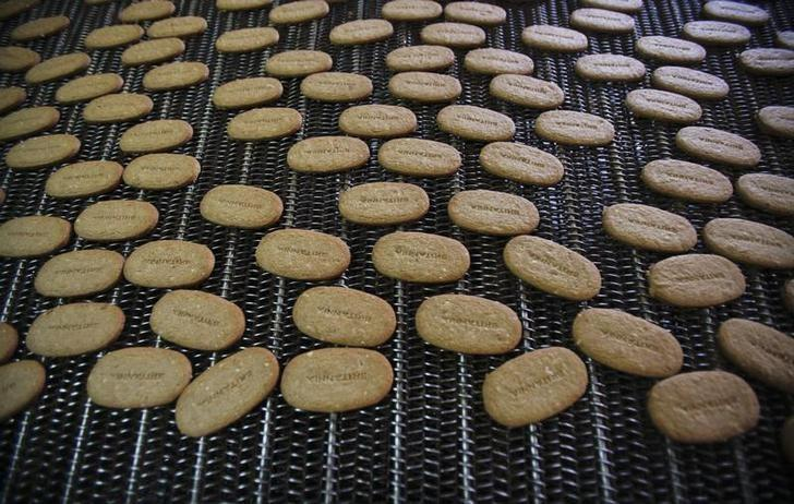 Biscuits pass along a conveyor belt after being baked at the Britannia factory in New Delhi June 3, 2011.  REUTERS/Adnan Abidi/Files