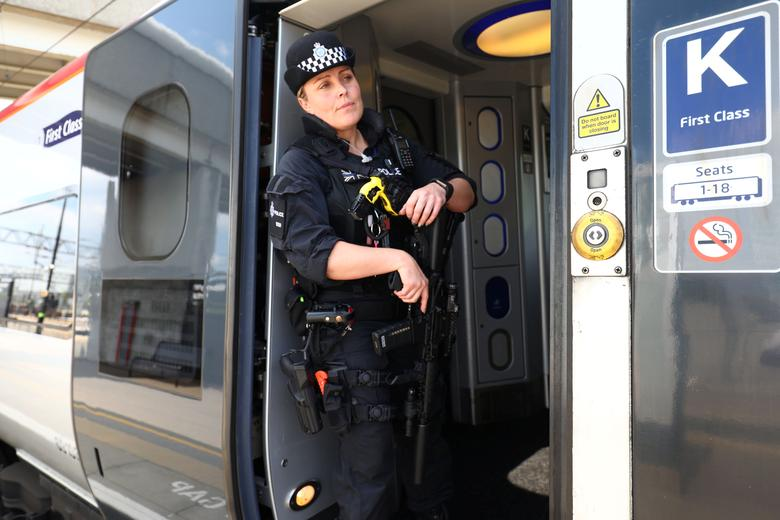 An armed police officer stands in a train at Milton Keynes station, Britain May 25, 2017. REUTERS/Neil Hall