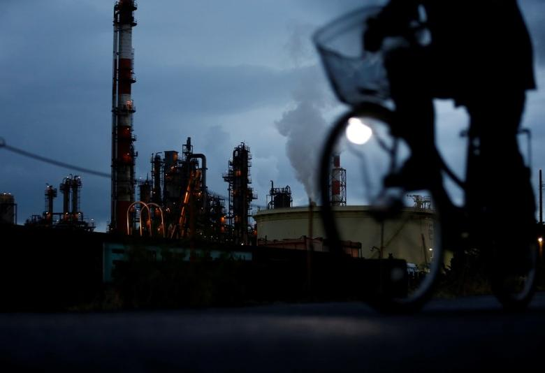 FILE PHOTO: A bicycle rider rides past a factory at Keihin industrial zone in Kawasaki, south of Tokyo, Japan, August 18, 2016. Picture taken on August 18, 2016.  REUTERS/Kim Kyung-Hoon/File Photo