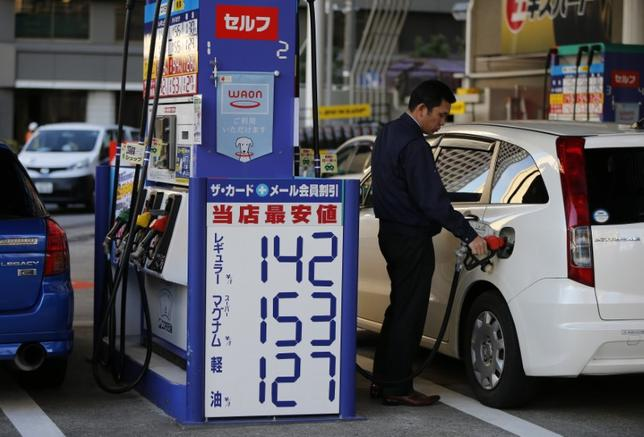 FILE PHOTO: A man refuels a vehicle next to a pricing quotation board at a petrol station in Tokyo December 17, 2014.   REUTERS/Issei Kato