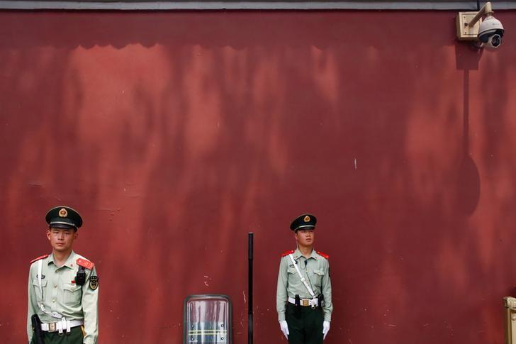 Paramilitary police officers stand underneath a security camera near Beijing's Tiananmen Square, China May 19, 2017.  REUTERS/Thomas Peter