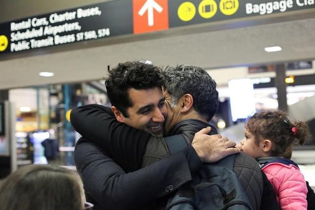 5月25日、トランプ米大統領が署名した大統領令で入国制限の対象となった7カ国の国民向けに4月に発給された一時ビザの数は、前年度平均を約50%下回った。写真はワシントン州のシアトル・タコマ空港で兄弟を出迎えたイラン人。2月撮影(2017年 ロイター/David Ryder)
