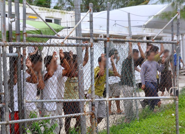 FILE PHOTO: Asylum-seekers look through a fence at the Manus Island detention centre in Papua New Guinea March 21, 2014. Faces pixellated at source. Picture taken March 21, 2014.      Eoin Blackwell/AAP/via REUTERS