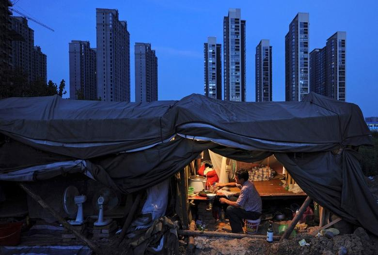 FILE PHOTO: A labourer has his dinner under his shed at a construction site of a residential complex in Hefei, Anhui province, August 1, 2012.  REUTERS/Stringer/File Photo