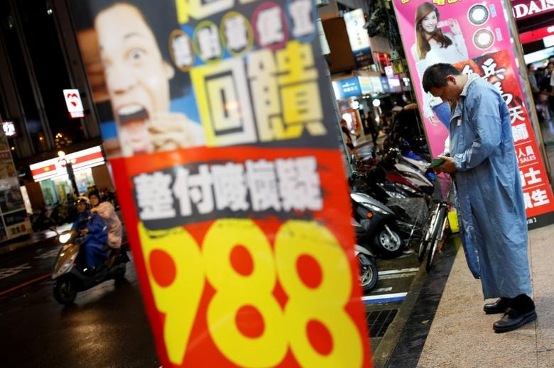 FILE PHOTO -  A man looks at his mobile phone at a shopping district in Taipei, Taiwan May 27, 2016. REUTERS/Tyrone Siu/File Photo