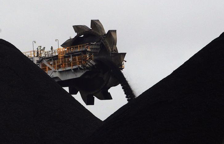 A reclaimer places coal in stockpiles at the coal port in Newcastle June 6, 2012. REUTERS/Daniel Munoz/Files
