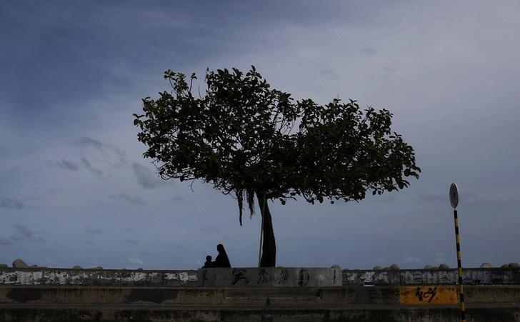 资料图片:2012年8月,马尔代夫首都马累,一名女子和她的女儿坐在海滩边的一棵树下。REUTERS/Adnan Abidi