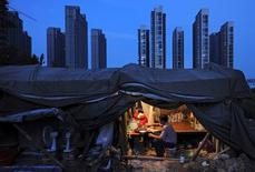 IMAGEN ARCHIVO: Un trabajador come en un sitio de construcción en Hefei, China. 1 de agosto 2012. Las reformas estructurales de China no serán suficientes para frenar el aumento de su deuda y otra rebaja a su calificación crediticia es posible a menos que limite su crédito, dijeron el viernes responsables de la agencia Moody's.  REUTERS/Stringer/File Photo