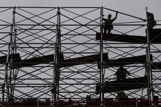 Los trabajadores desmantelan los andamios en un proyecto de construcción en Manhattan, Nueva York.  24 de mayo 2017. El crecimiento económico en Estados Unidos se desaceleró menos a lo estimado inicialmente en el primer trimestre, pero la debilidad probablemente fue una anormalidad en un mercado laboral fuerte que está cerca del empleo pleno.   REUTERS/Carlo Allegri