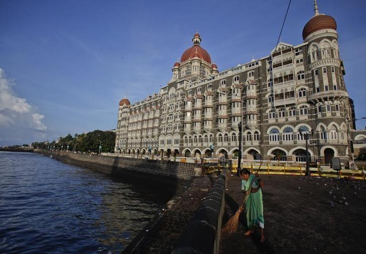 A municipal worker sweeps a pavement in front of the Taj Mahal hotel in Mumbai May 31, 2011. REUTERS/Vivek Prakash/Files