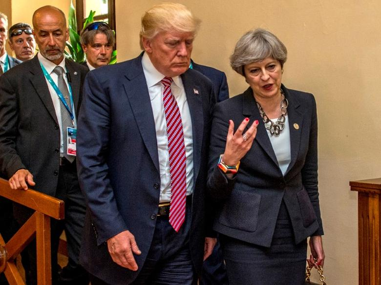 U.S President Donald Trump walks with British Prime Minister Theresa May at the G7 summit in Taormina, Sicily, Italy, in this photo released by the British government, May 26, 2017. British government/Handout via REUTERS