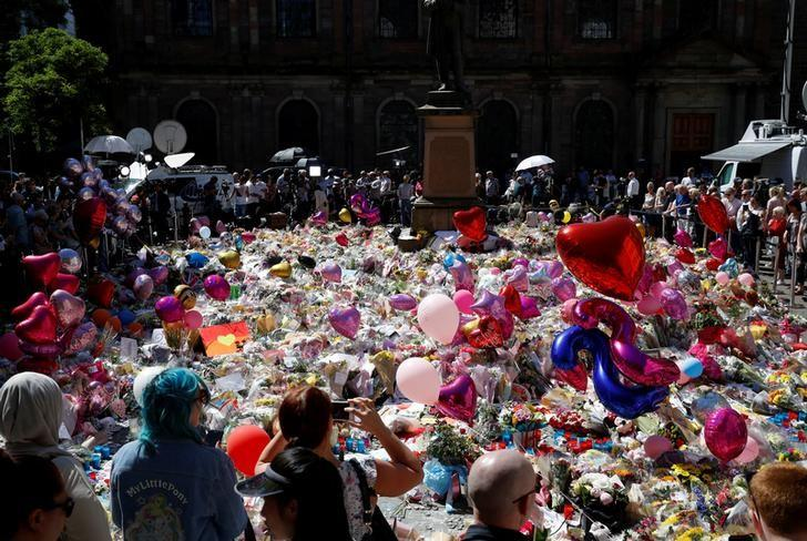 People look at tributes to the victims of the attack on the Manchester Arena, in central Manchester, Britain May 26, 2017. REUTERS/Phil Noble