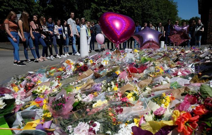 Pupils look on at the flowers left outside Tottington high school, in memory of pupil Olivia Campbell who was killed during the Manchester Arena attack, Bury, Manchester, Britain, May 26, 2017. REUTERS/Andrew Yates
