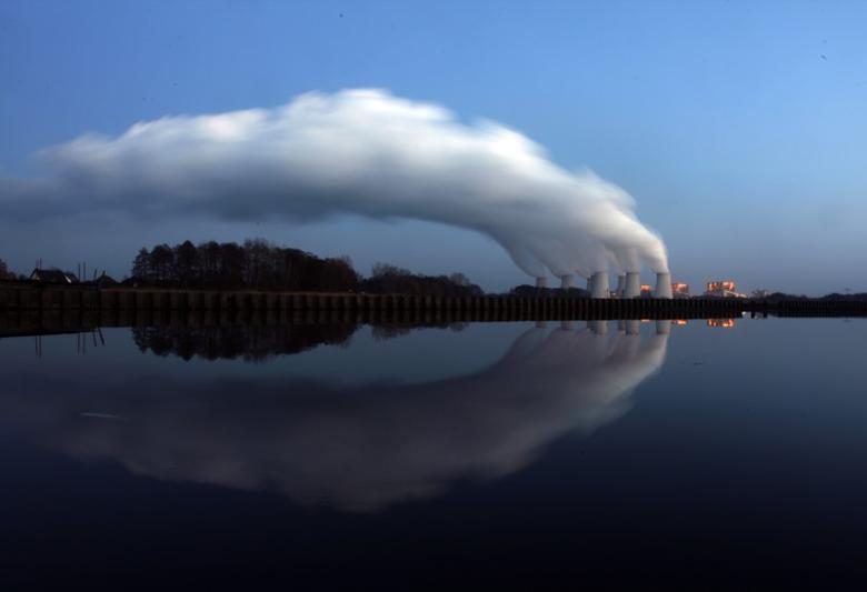 Steam billowing from the cooling towers of Vattenfall's Jaenschwalde brown coal power station is reflected in the water of a lake near Cottbus, eastern Germany December 2, 2009. REUTERS/Pawel Kopczynski