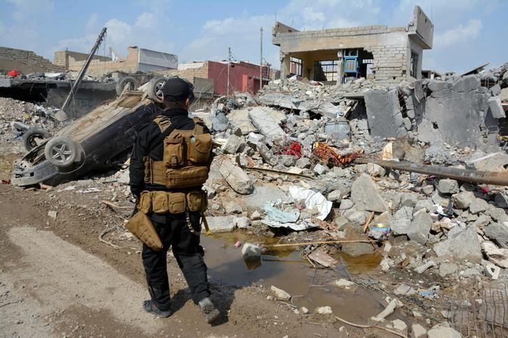 FILE PHOTO: A member of the Counter Terrorism Service (CTS) walks at the site after an air strike attack against Islamic State triggered a massive explosion in Mosul, Iraq March 29, 2017. REUTERS/Stringer/File Photo
