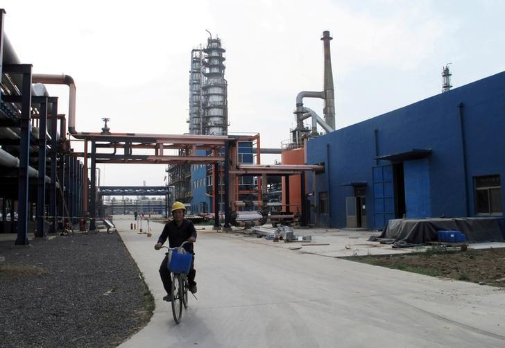 FILE PHOTO: An employee rides a bike on a road near refinery plants of Chambroad Petrochemicals, in Boxing, Shandong Province, China, May 10, 2016. REUTERS/Meng Meng/File Photo