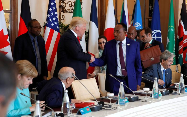 U.S. President Donald Trump (C) greets Niger's President Mahamadou Issoufou as they arrive to take their places at an expanded session during the G7 Summit in Taormina, Sicily, Italy, May 27, 2017.  REUTERS/Philippe Wojazer