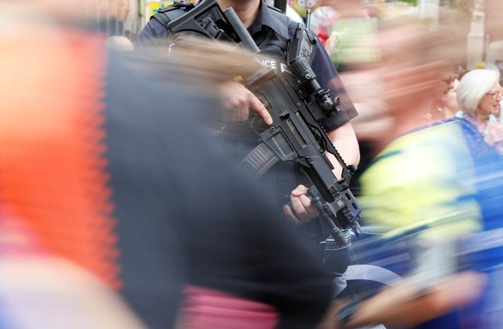 Runners pass an armed police officer during a 10k run in central Manchester, Britain, May 28, 2017. REUTERS/Phil Noble/files