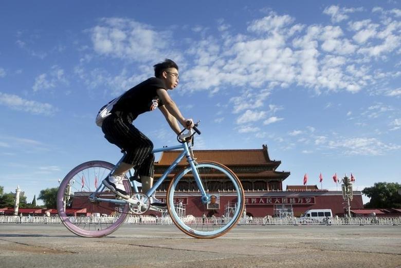 资料图片:2015年8月,北京,一名男子清晨骑车经过天安门。REUTERS/Jason Lee